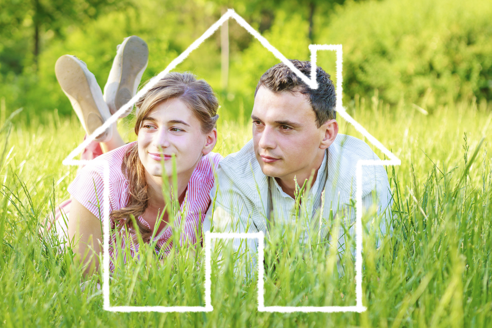 Young couple lying on grass dreaming to a house wondering what AC seer ratings are